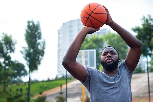 Homem barbudo jogando uma bola para aro de tiro médio