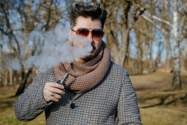 Homem barbudo jovem confiante em cigarro eletrônico de vape de óculos de sol. um homem jovem bonito barbudo hipster vaping cigarro ao ar livre no parque. fechar-se.