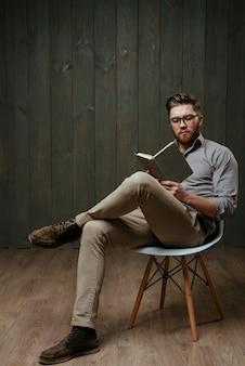Homem barbudo jovem e bonito concentrado de óculos sentado e lendo um livro isolado em uma superfície de madeira preta