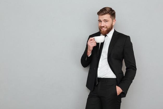 Homem barbudo legal satisfeito em terno bebendo chá