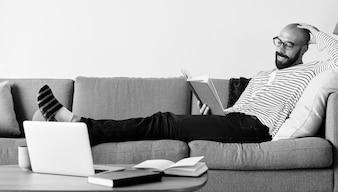 Homem barbudo lendo no sofá