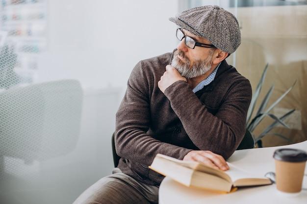 Homem barbudo lendo um livro e sentado à mesa