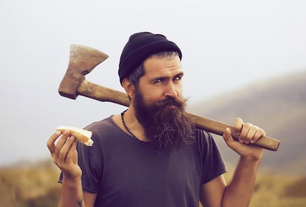 Homem barbudo lenhador hipster com barba e bigode com machado comendo pão no topo da montanha