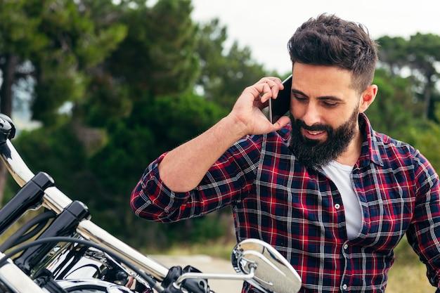 Homem barbudo ligando de moto em seu telefone