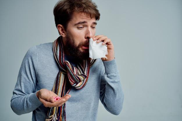 Homem barbudo limpando o nariz com um lenço problemas de saúde luz de fundo