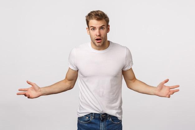 Homem barbudo loiro atraente em camiseta branca com as mãos espalhadas