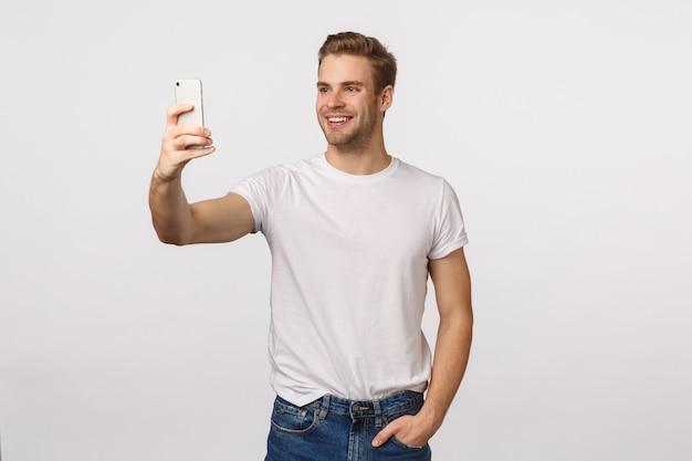 Homem barbudo loiro atraente em camiseta branca tomando selfie