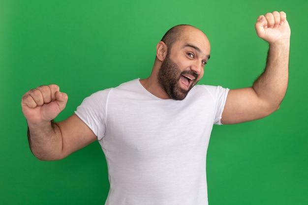 Homem barbudo louco e feliz em uma camiseta branca sorrindo alegremente levantando os punhos em pé sobre a parede verde