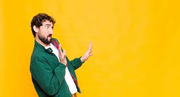 Homem barbudo louco jovem contra o espaço da cópia de parede laranja.