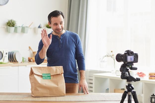 Homem barbudo maduro acenando enquanto grava uma crítica sobre o serviço de entrega de comida no interior da cozinha