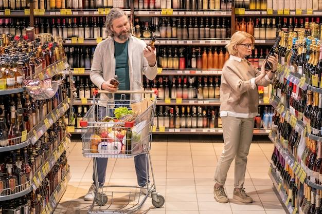 Homem barbudo maduro com carrinho de compras escolhendo uma garrafa de conhaque na prateleira do departamento de bebidas alcoólicas enquanto sua esposa toma champanhe