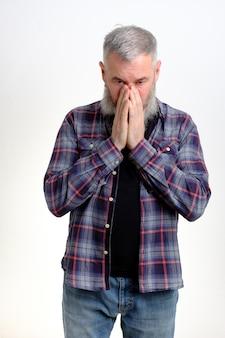 Homem barbudo maduro de mãos dadas implorando por perdão em apuros, pedindo ajuda, isolado na parede branca