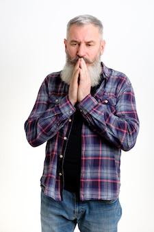 Homem barbudo maduro de mãos dadas implorando por perdão em apuros, pedindo ajuda, isolado no fundo branco