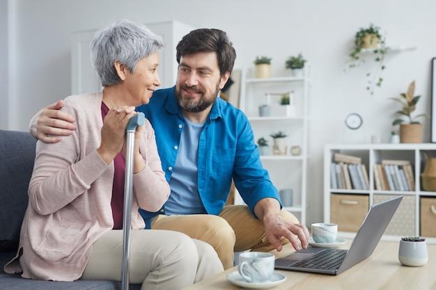 Homem barbudo maduro ensinando uma mulher idosa a usar um laptop enquanto elas estão sentadas no sofá na sala de casa