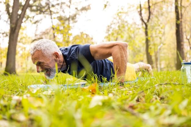 Homem barbudo maduro fazendo flexões na natureza