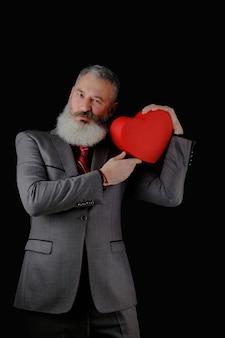 Homem barbudo maduro usa terno cinza segurando uma caixa de presente em forma de coração vermelho, fundo preto isolado