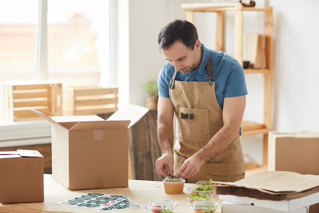 Homem barbudo maduro usando avental embalando porções individuais de comida, trabalhador em serviço de entrega de comida