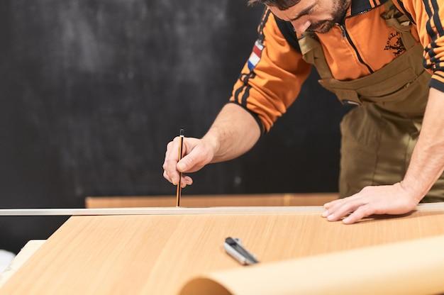 Homem barbudo, marcando uma madeira com um lápis com um rosto de concentração