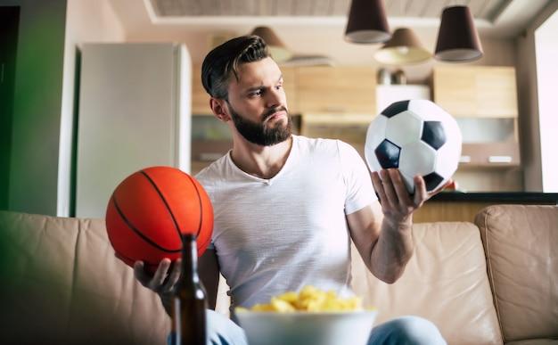 Homem barbudo moderno animado e bonito relaxando no sofá enquanto assiste a uma partida de futebol na tv