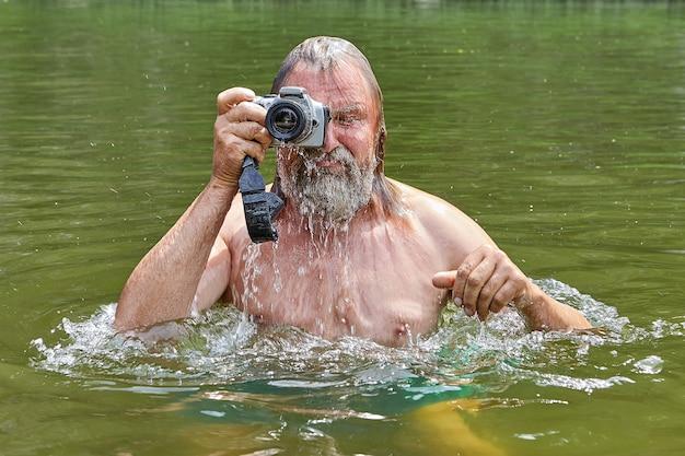 Homem barbudo molhado maduro com câmera à prova d'água nas mãos está nadando no rio e tirando fotos durante suas férias.