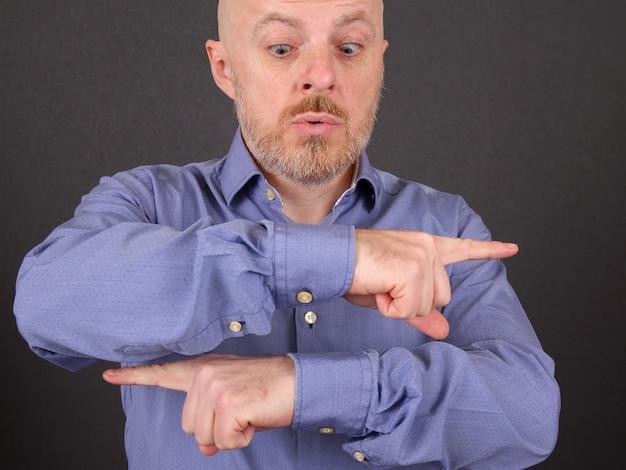 Homem barbudo mostra os dedos indicadores em diferentes direções