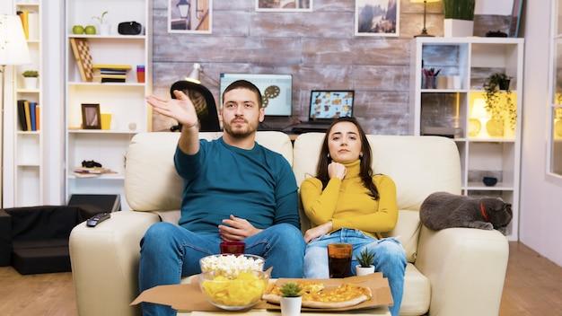 Homem barbudo mudando de canal de tv com gestos com as mãos enquanto sua namorada e o gato estão ao lado dele no sofá.
