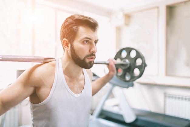 Homem barbudo musculoso durante treino no ginásio. fisiculturista fazendo levantamento de peso. feche de jovem modelo atlético feminino treina no centro de fitness.