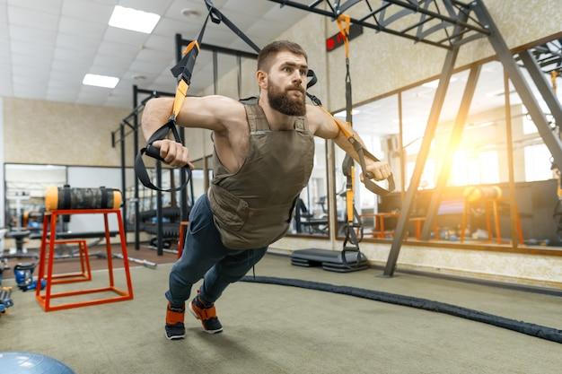Homem barbudo musculoso, vestido com colete blindado ponderado militar, fazendo exercícios