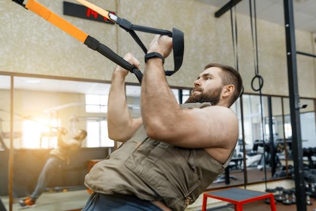 Homem barbudo musculoso vestido militar colete blindado ponderado fazendo exercícios