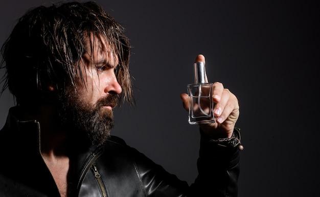 Homem barbudo na jaqueta de couro com frasco de perfume ou colônia. publicidade de cosméticos.