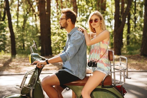 Homem barbudo na scooter com a namorada ao ar livre