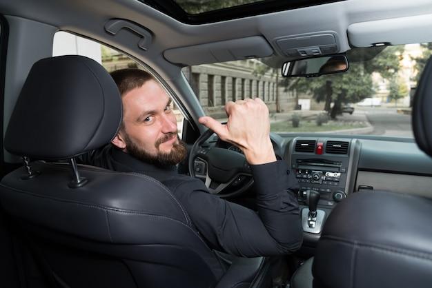 Homem barbudo no carro mostra um gesto.