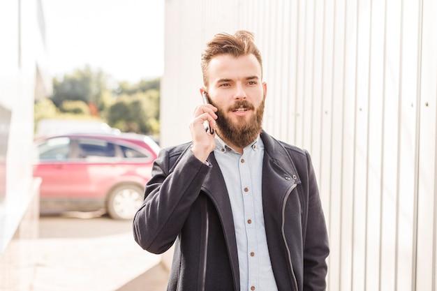 Homem barbudo no casaco preto falando no smartphone