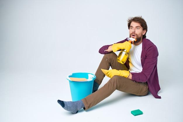 Homem barbudo no chão limpando material de limpeza doméstico
