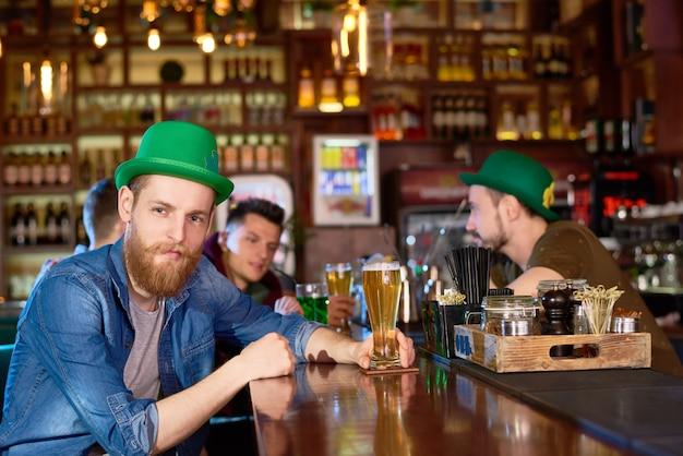 Homem barbudo no chapéu-coco verde