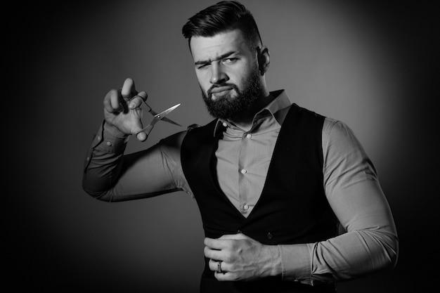 Homem barbudo no colete sobre fundo vermelho. os homens cortam a barba com uma tesoura de cabeleireiro. preto e branco