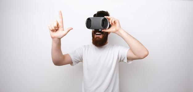Homem barbudo olhando através do dispositivo vr tocando algo com um dedo.