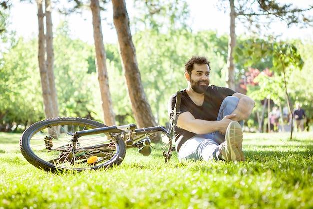 Homem barbudo, olhando para longe da câmera com sua bicicleta ao lado dele no parque. esporte e saúde