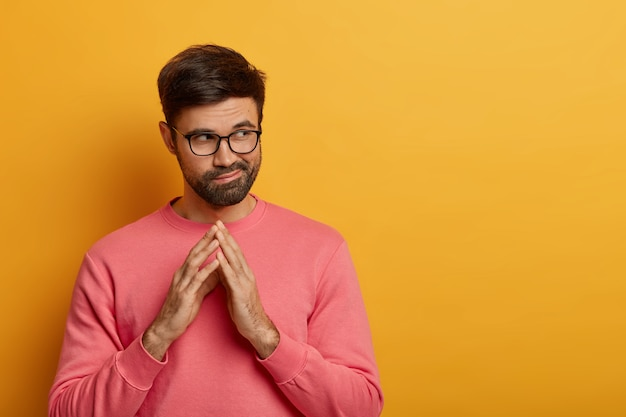 Homem barbudo pensativo e complicado fecha os dedos, tem alguma intenção em mente, considera planos para o futuro, olha para o lado misteriosamente, tem esquema, usa suéter rosado, isolado sobre parede amarela
