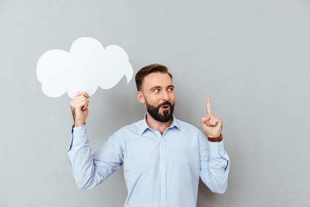 Homem barbudo pensativo em roupas de negócios segurando a nuvem do discurso em branco