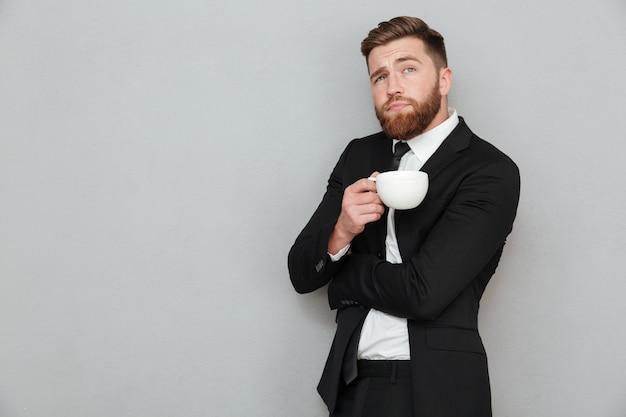 Homem barbudo pensativo em segurar a xícara de café