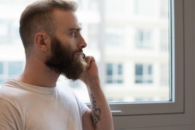 Homem barbudo pensativo falando no telefone e olhando pela janela