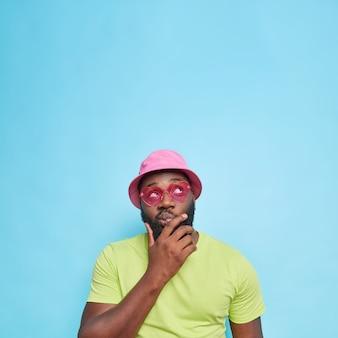 Homem barbudo pensativo segura o queixo focado acima, considera que algo toma decisão usa óculos de sol rosa com roupa de verão isolados sobre a parede azul