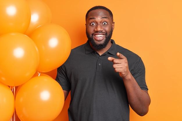 Homem barbudo positivo com barba espessa sorri positivamente aponta o dedo indicador diretamente para você segura um monte de balões inflados usa uma camiseta preta isolada sobre uma parede laranja vívida