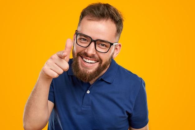 Homem barbudo positivo com óculos apontando