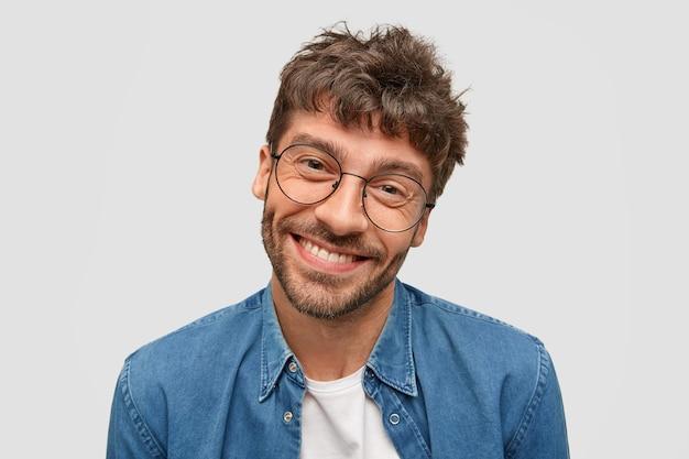 Homem barbudo positivo com sorriso amigável, estando em alto astral enquanto passa o tempo livre