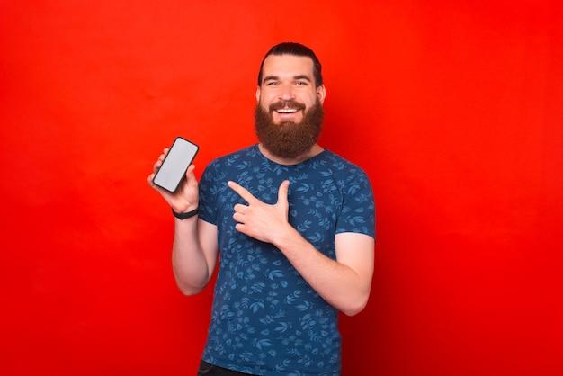 Homem barbudo positivo está apresentando algo na tela do telefone.