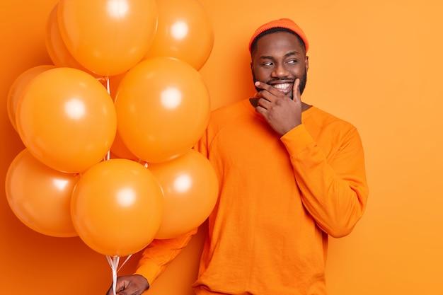 Homem barbudo positivo segura um monte de balões celebra a ocasião festiva, usa um macacão casual e um chapéu isolado na parede laranja estando na festa
