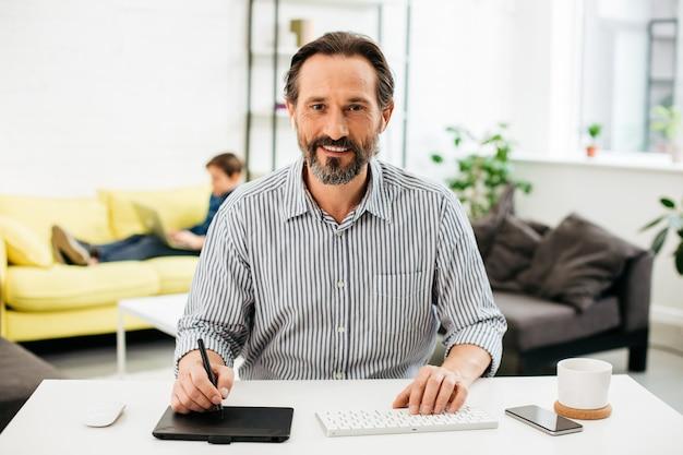 Homem barbudo positivo sentado à mesa em casa e sorrindo enquanto usa o teclado sem fio e uma caneta com tablet gráfico