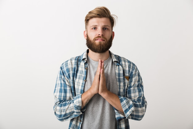 Homem barbudo preocupado, vestido com uma camisa xadrez, isolado, implorando por algo